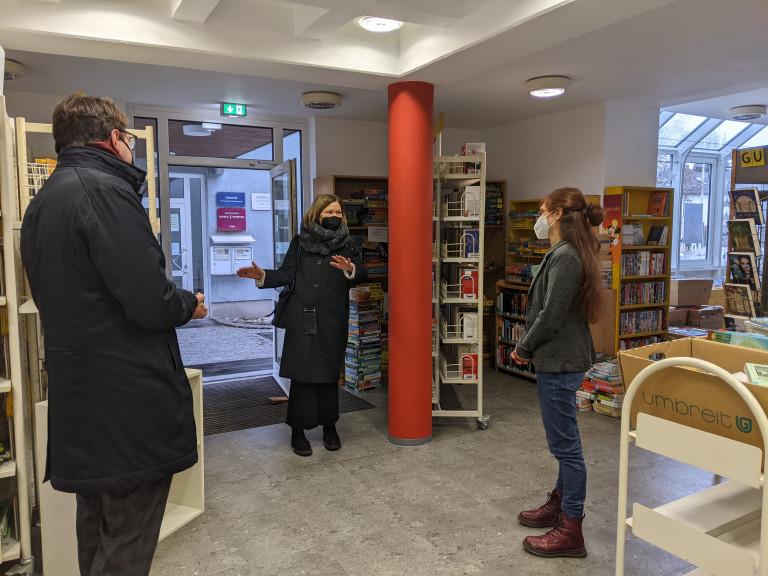 Wild und Koch lassen sich Bücherei-Leiterin Karin Rangwich über Click and Collect informieren